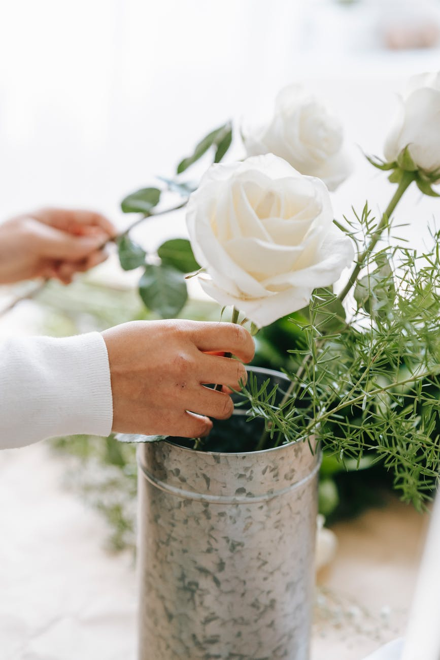 crop florist making bouquet of blooming roses and plant sprig