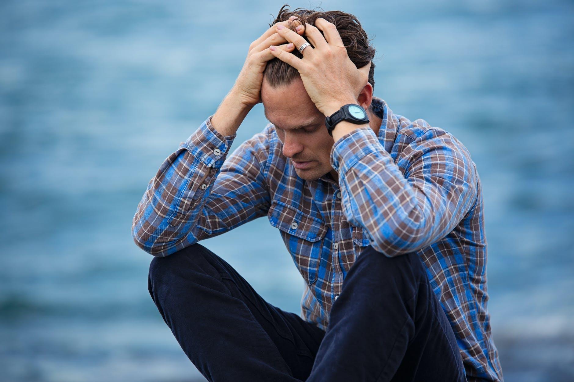 man in blue and brown plaid dress shirt touching his hair